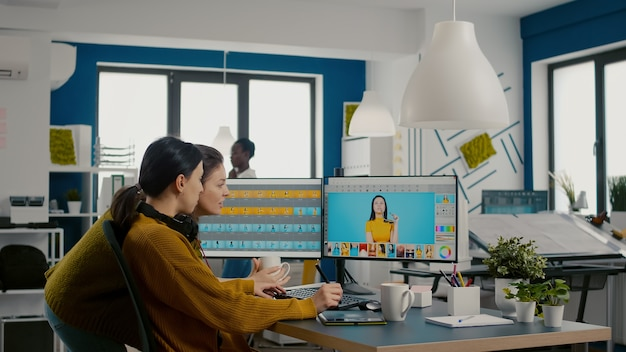Two photographers advising for retouching client photo in creative media agency office graphic desig...
