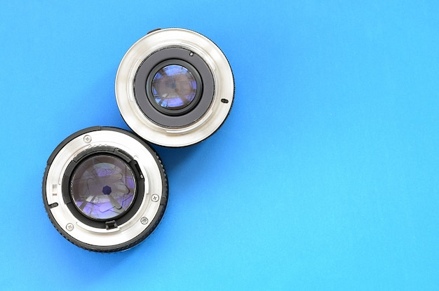 Two photographic lenses lie on a bright blue background. space for text