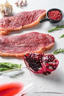 로즈마리와 석류석을 곁들인 피칸하 쇠고기 스테이크 2개, 흰색 배경, 측면 보기.