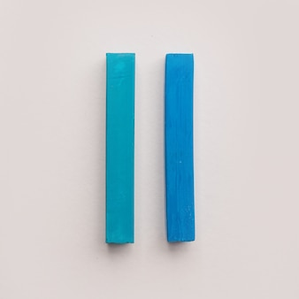 Two pieces of blue pastel crayon chalks