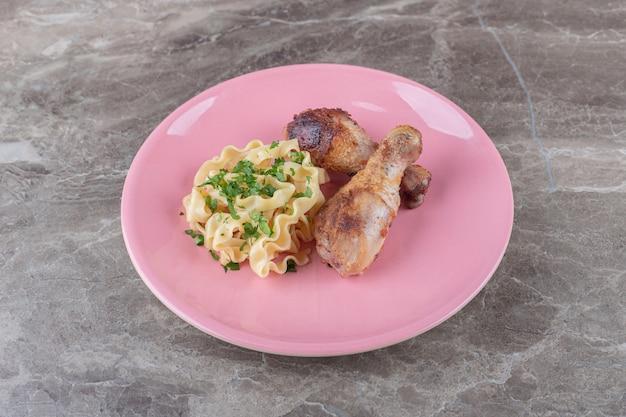 Due pezzi di coscia accanto alla pasta su un piatto, sul marmo.