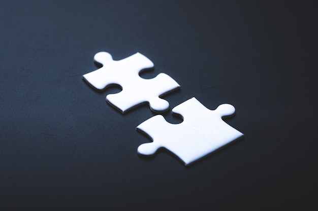 Two pieces of jigsaw puzzle or autism puzzle piece symbol