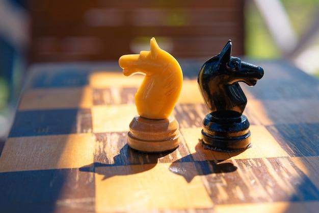 古いチェス盤に描かれた白と黒のチェスナイトの2枚。