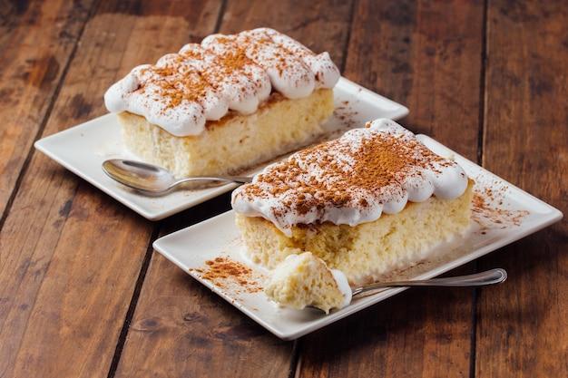 木製の背景においしい3つのミルクケーキデザートの2つの部分