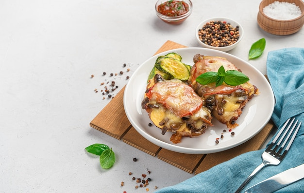 きのこ、トマト、チーズを添えた焼き鳥の胸肉2枚と、明るい灰色の背景にズッキーニのおかず。側面図、コピー用のスペース。
