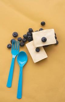 파스텔 배경에 파란색 스푼과 포크 옆에 블루베리 치즈 파이 두 조각