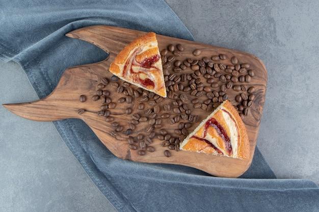 木製のまな板にコーヒー豆とケーキ2枚