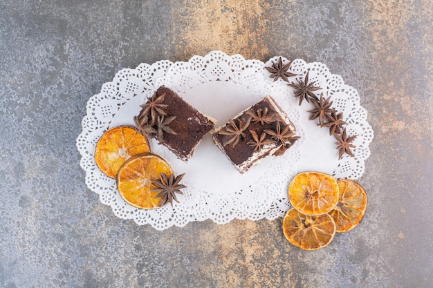 Два куска торта с сушеным апельсином и звездчатым анисом на белой поверхности