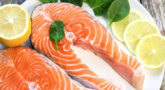 회색 나무 배경에 시금치와 레몬을 넣은 하얀 접시에 신선한 연어 스테이크 두 조각. 오메가 3 비타민, 건강한 생활 방식. 천연 채식 음식. 평면도.
