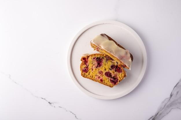Два куска домашнего кекса с клюквой и сахарной пудрой на белой тарелке на свету