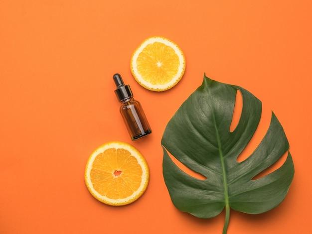 오렌지 두 조각, 스포이드가 있는 병, 오렌지 배경에 몬스테라 한 장. 플랫 레이.
