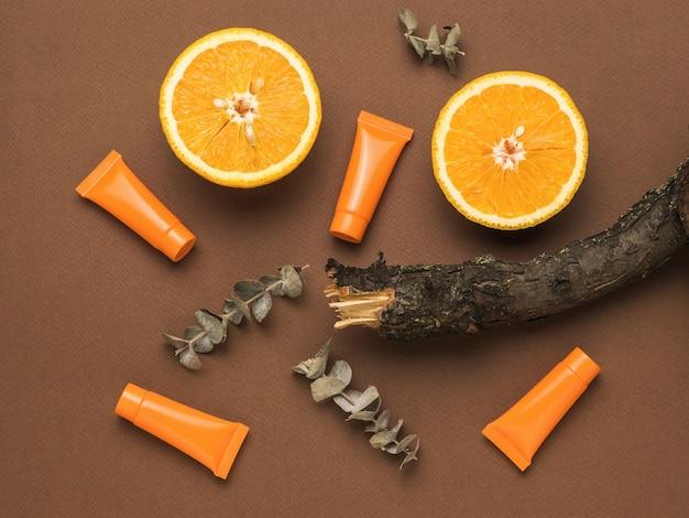 Два кусочка апельсина, ветка старого дерева, ветки эвкалипта и тюбики сливок на коричневом фоне. косметика и лечебные мази на основе природных минералов. плоская планировка.