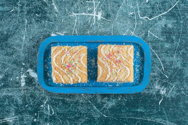 파란색 배경에 나무 접시에 롤 케이크 두 조각. 고품질 사진