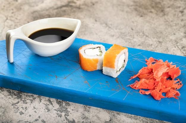Два кусочка суши-роллов с лососем и имбирем на синей доске.