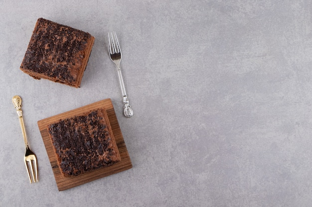 돌 테이블에 달콤한 초콜릿 케이크 두 조각.