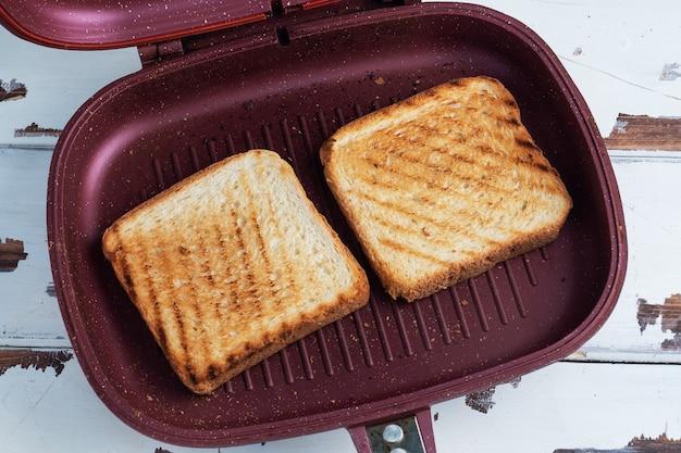 グリルパンで焼いた 2 枚のパン。閉じる。