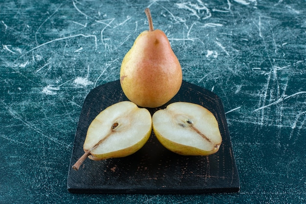 Due pezzi di pere sulla tavola, su sfondo blu. foto di alta qualità