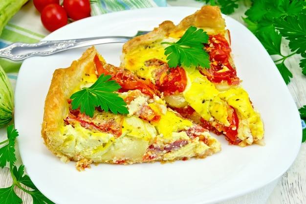 ナプキンの白い皿にトマトと卵を入れたズッキーニの 2 ピースのパイ、明るい木の板の背景にパセリ