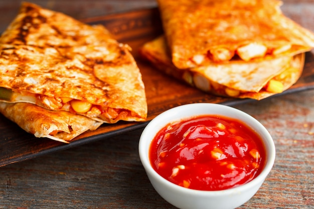 Two pieces of quesadilla on a plate and sauce of salsa on a wooden background.