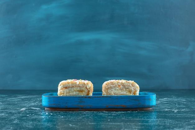 Due pezzi di torta del rotolo sul piatto di legno, sui precedenti blu. foto di alta qualità