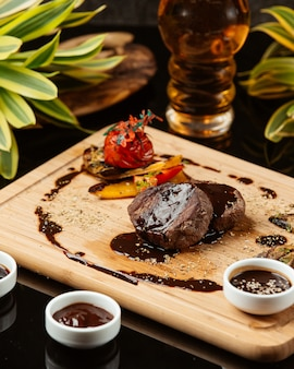 Two pieces of round small steaks with pomegranate sauce and grilled vegetables
