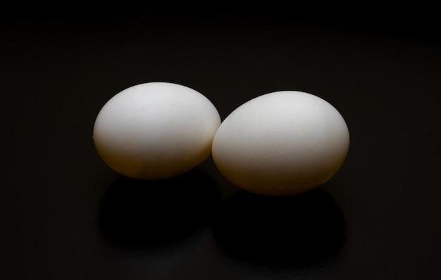 Два голубиных яйца крупным планом вид сверху на темном фоне