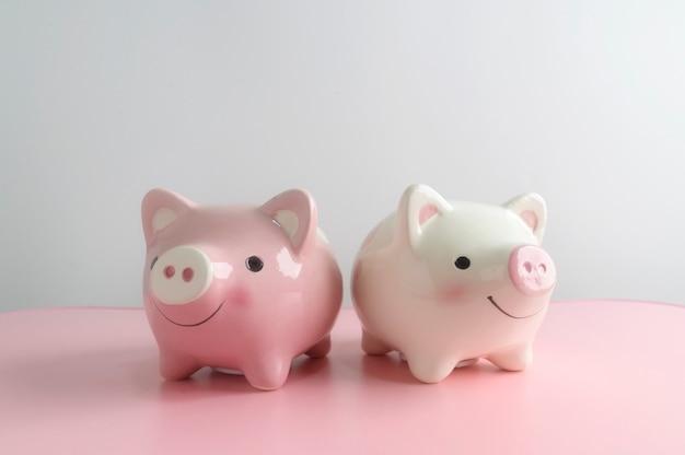 白地にピンクのテーブルの上の2つの貯金箱。将来の投資コンセプトのための節約お金。