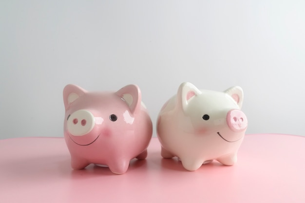 Two piggy bank on pink table with white background. a saving money for future investment concept.