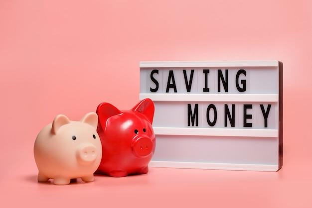 Две копилки и табличка с надписью «экономия денег». копилки на розовом фоне. концепция домашнего бюджета.