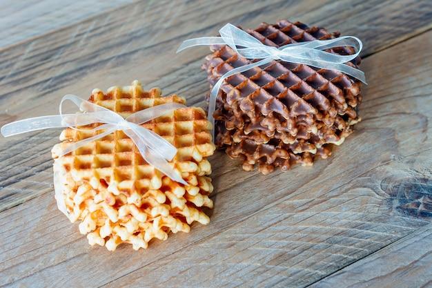 木製のテーブルに蜂蜜とチョコレートを添えたおいしいベルギーワッフルの2つの山。