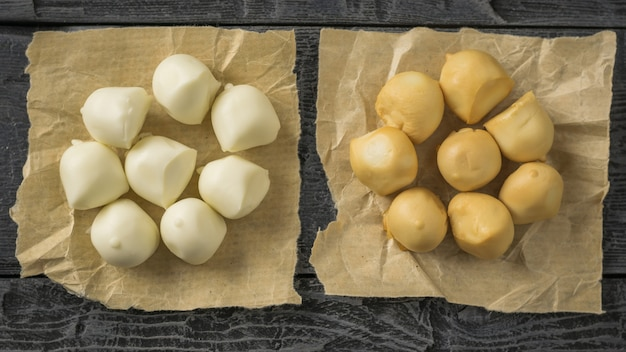暗い木製のテーブルの上の紙の上に作りたてのモッツァレラチーズの2つの山