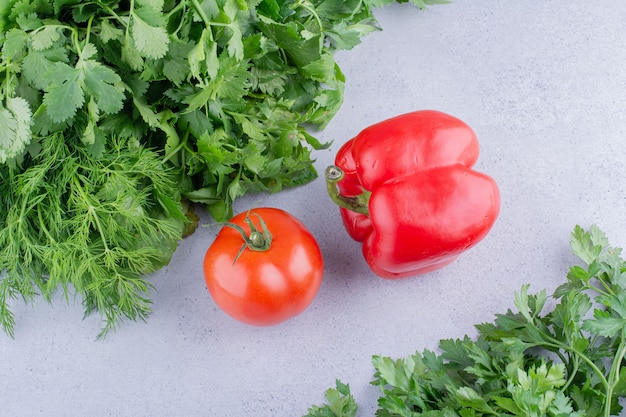 Two piles of various greens with tomato and pepper in between on marble background. high quality photo