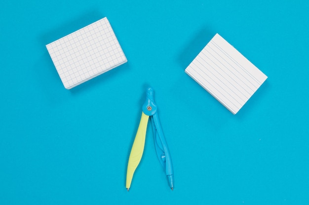 Two piles of white scratch paper and a compass in the middle
