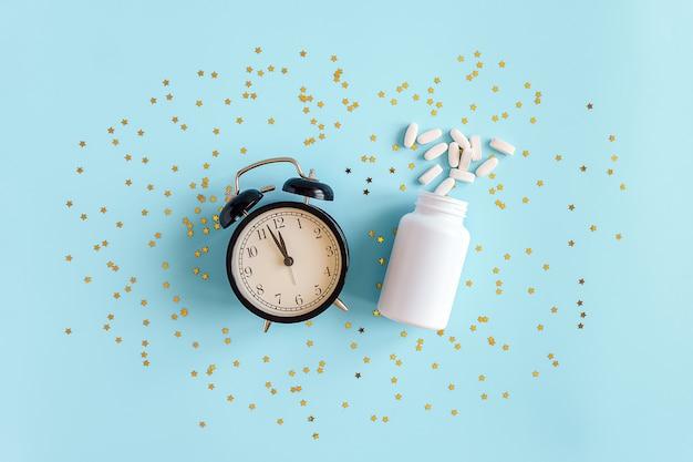 두 알 약, 흰색 병, 검은 알람 시계와 금색 별 색종이. 개념 불면증, 수면 문제, 수면제 멜라토닌 복용 시간. 평면도 평평한 복사 공간