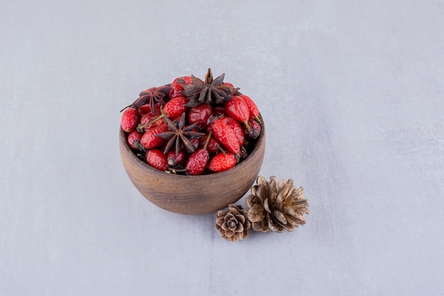 Two pine cones next to wooden bowl of hips and anise on white background.