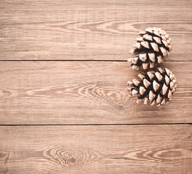Two pine cones on a wooden table. christmas mystery. copy space.