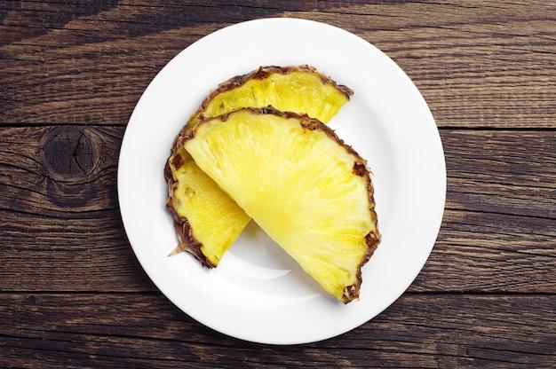 Два ломтика ананаса в тарелке на столе