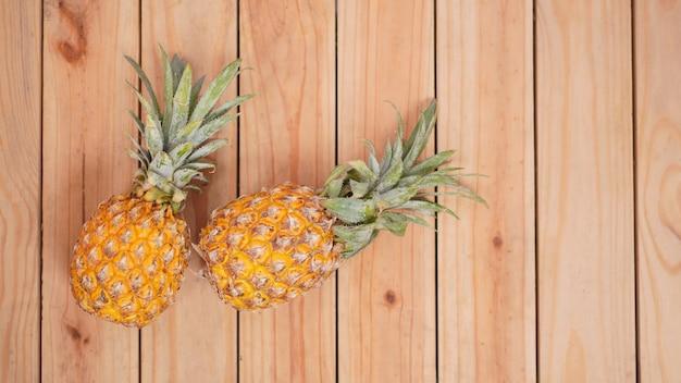 木製の背景に2つのパイナップル