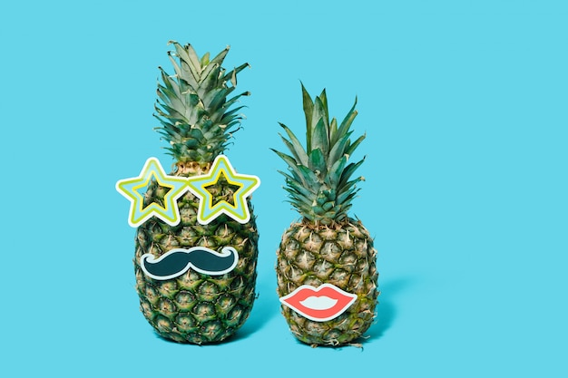 Two pineapples with glued lips and mustache on a blue background.. party and date concept.