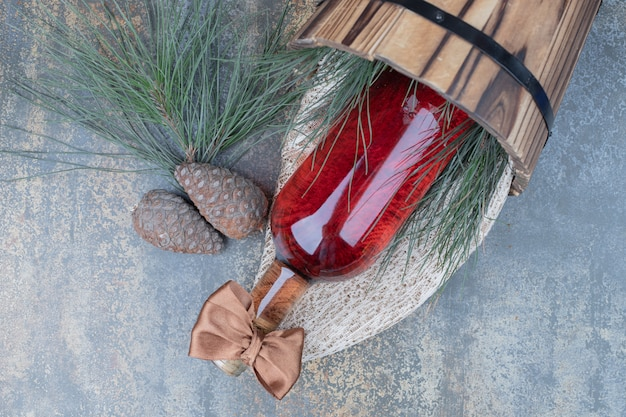 大理石の背景にワインのボトルと2つの松ぼっくり。高品質の写真