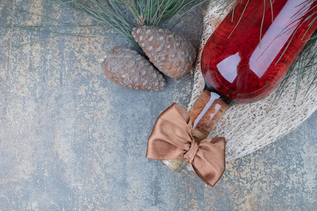 Two pinecones with bottle of wine on marble table.