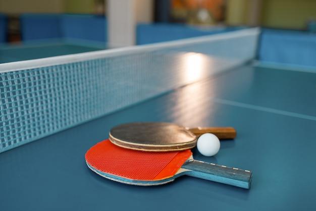 그물, 아무도, 근접 촬영보기와 함께 테이블에 두 개의 탁구 패들. 탁구 클럽, 테니스 개념