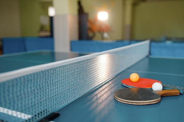 그물, 아무도, 근접 촬영보기와 게임 테이블에 두 개의 탁구 라켓과 공. 탁구 클럽, 테니스 컨셉, 탁구