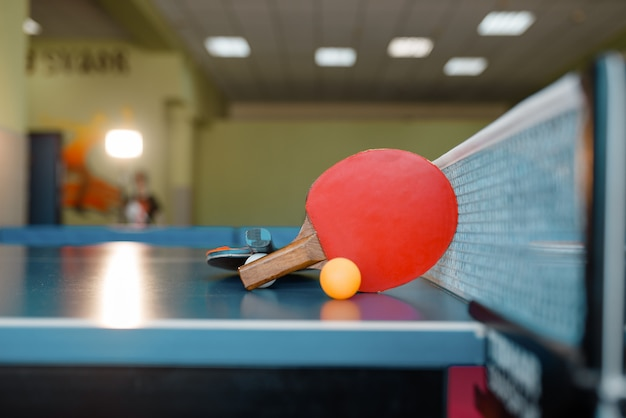 Two ping pong rackets and ball on the table with net