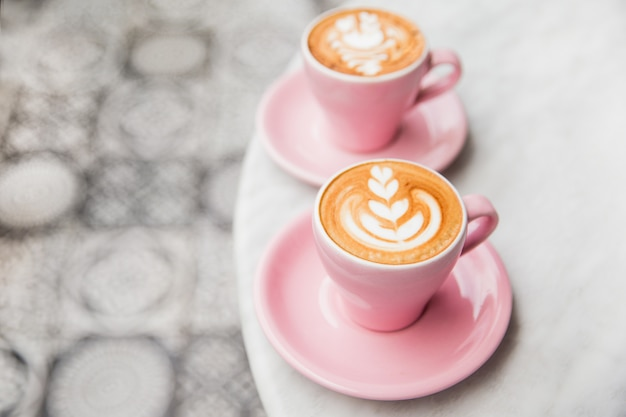 Two pink cups of cappuccino with beautiful latte art on marble table.
