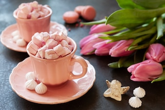Two pink cups with pink heart shaped marshmallows