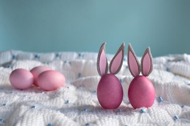 Два розовых пасхальных яйца с крупным планом ушей кролика на белом связанном пледе и синем фоне. счастливой пасхи