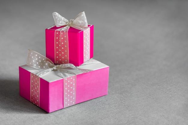 Две розовые подарочные коробки, обернутые белыми бантами на нейтральном сером фоне