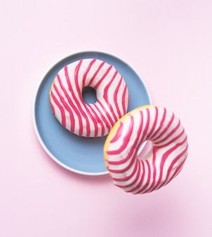 Two pink glazed  donut flying in blue plate in pink background