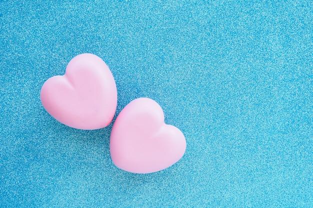 Два розовых блестящих сердца на синем блестящем фоне